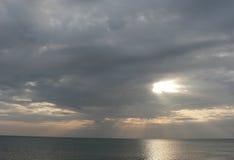 Ηλιοβασίλεμα στη θάλασσα με τον γκρίζο νεφελώδη ουρανό, ακτίνες του φωτός Στοκ Φωτογραφία