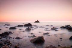 Ηλιοβασίλεμα στη δύσκολη ακτή της θάλασσας Χαμηλή ταχύτητα παραθυρόφυλλων για την ομαλή στάθμη ύδατος και την ονειροπόλο επίδραση Στοκ Φωτογραφία