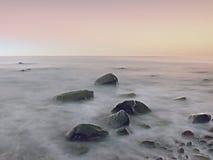 Ηλιοβασίλεμα στη δύσκολη ακτή της θάλασσας Χαμηλή ταχύτητα παραθυρόφυλλων για την ομαλή στάθμη ύδατος και την ονειροπόλο επίδραση Στοκ Εικόνες