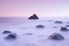 Ηλιοβασίλεμα στη δύσκολη ακτή της θάλασσας Χαμηλή ταχύτητα παραθυρόφυλλων για την ομαλή στάθμη ύδατος και την ονειροπόλο επίδραση Στοκ φωτογραφία με δικαίωμα ελεύθερης χρήσης