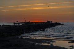 Ηλιοβασίλεμα στον κυματοθραύστη Στοκ Φωτογραφίες