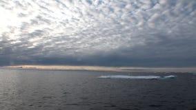 Ηλιοβασίλεμα στον ωκεανό μεταξύ των παγόβουνων και τον πάγο στην Αρκτική φιλμ μικρού μήκους