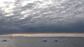 Ηλιοβασίλεμα στον ωκεανό μεταξύ των παγόβουνων και τον πάγο στην Αρκτική απόθεμα βίντεο