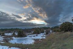 Ηλιοβασίλεμα στο χειμερινό δάσος με το δραματικό γκρίζο ουρανό και την παγωμένη λίμνη Ρωσία, Stary Krym Στοκ φωτογραφίες με δικαίωμα ελεύθερης χρήσης