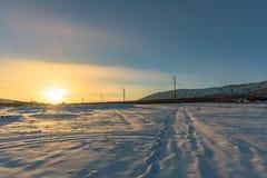 Ηλιοβασίλεμα στο χιονισμένο τομέα και το δρόμο που οδηγεί στο δάσος κάτω από το βουνό Ρωσία, Stary Krym Στοκ Εικόνες