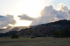Ηλιοβασίλεμα, σύννεφα και βουνά Στοκ Εικόνες