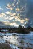 Ηλιοβασίλεμα το χειμώνα Χριστουγέννων με το δραματικό συννεφιάζω ουρανό και την παγωμένη λίμνη Ρωσία, Stary Krym Στοκ Εικόνα