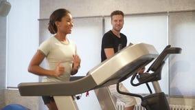 Η ισπανική γυναίκα εκπαιδεύει treadmill, μιλά και φλερτάρει με τον ισχυρό χαμογελώντας άνδρα που πλησίον φιλμ μικρού μήκους