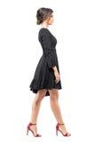 Η ισπανική γυναίκα στο μαύρο φόρεμα και το κόκκινο υψηλά βάζει τακούνια στα σανδάλια περπατώντας κοιτάζοντας μπροστά την πλάγια ό στοκ φωτογραφίες με δικαίωμα ελεύθερης χρήσης