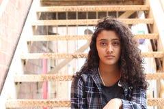 Η ισπανική νέα γυναίκα με τη σγουρή τρίχα κάθεται στα σκαλοπάτια Στοκ Φωτογραφία