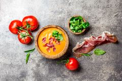 Η ισπανική σούπα Salmorejo ντοματών εξυπηρέτησε στο ξύλινο κύπελλο ελιών με το serrano ζαμπόν jamon στο υπόβαθρο πετρών Τοπ όψη Στοκ Φωτογραφία