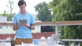 Ηλιόλουστη ημέρα, άτομο που στέκεται και που κοιτάζει βιαστικά στην ταμπλέτα στο μπαλκόνι, συσκευή απόθεμα βίντεο