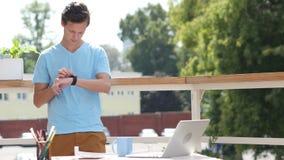 Ηλιόλουστη ημέρα, άτομο που στέκεται και που χρησιμοποιεί Smartwatch στο μπαλκόνι, συσκευή φιλμ μικρού μήκους