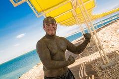 Ηλιόλουστη ημέρα στη νεκρή θάλασσα - το άτομο μεταχειρίστηκε με τη λάσπη Στοκ Φωτογραφίες