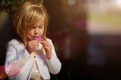 Ηλιόλουστη ημέρα, το μικρό κορίτσι βρίσκεται στη χλόη Στοκ Φωτογραφίες