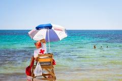 Ηλιόλουστη μεσογειακή παραλία, lifeguard συνεδρίαση στη θέση παρατήρησης Στοκ Εικόνα
