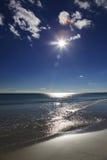Ηλιόλουστη παραλία με την άμμο, τα κύματα, τα σύννεφα και το μπλε ουρανό Στοκ Εικόνες