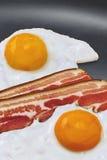 Ηλιόλουστη πλευρά επάνω στα αυγά και τις φέτες μπέϊκον στο τηγάνι τηγανητών Στοκ φωτογραφία με δικαίωμα ελεύθερης χρήσης