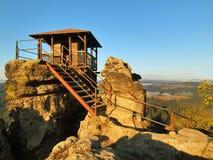 Ηλιόλουστη σκηνή πρωινού φθινοπώρου Ξύλινη καμπίνα στην κύρια αιχμή του βράχου ως σημείο άποψης, σκοτεινός ουρανός, υδρονέφωση φθ Στοκ Φωτογραφία