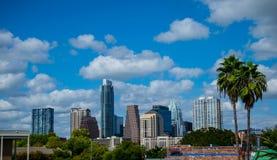 Ηλιόλουστος μπλε ουρανός ημέρας οριζόντων του Ώστιν Τέξας παραδείσου με δύο τροπικούς φοίνικες στοκ φωτογραφία