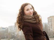 Ηλιόλουστο κορίτσι με το muffer με sity στην πλάτη Στοκ Εικόνες