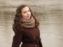 Ηλιόλουστο κορίτσι στο παλτό με τη μικρή λίμνη στην πλάτη Στοκ φωτογραφία με δικαίωμα ελεύθερης χρήσης