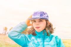 Ηλιόλουστο πορτρέτο του χαριτωμένου κοριτσιού στη μπλε ζακέτα και της ΚΑΠ με τον αέρα στην τρίχα της Στοκ Εικόνα