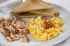 Ηλιόλουστο πρόγευμα με το μπέϊκον, τα αυγά και το ψωμί Στοκ Φωτογραφίες