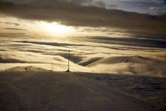 Η κάθοδος σε ένα χιονοδρομικό κέντρο, το βουνό είναι επάνω από τα σύννεφα ηλιοβασιλέματος, οι πτώσεις σκοταδιού στοκ εικόνα