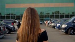 Η κάμερα ακολουθεί ένα νέο ελκυστικό brunette στο χώρο στάθμευσης φιλμ μικρού μήκους