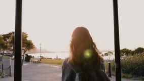 Η κάμερα ακολουθεί την ευτυχή περιστασιακή νέα γυναίκα με το σακίδιο πλάτης, τρίχα που φυσά στον αέρα περπατώντας κατά μήκος του  φιλμ μικρού μήκους