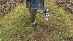 Η κάμερα ακολουθεί τον κηπουρό γυναικών με τον κόπτη κλάδων φιλμ μικρού μήκους