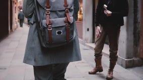 Η κάμερα ακολουθεί το μοντέρνο τουρίστα επιχειρηματιών που φορά το κοστούμι με το σακίδιο πλάτης περπατώντας στην παλαιά οδό στη  απόθεμα βίντεο