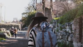 Η κάμερα ακολουθεί το νέο θηλυκό ταξιδιώτη στο καπέλο με το σακίδιο πλάτης που ερευνά τις καταστροφές του φόρουμ στη Ρώμη, Ιταλία φιλμ μικρού μήκους