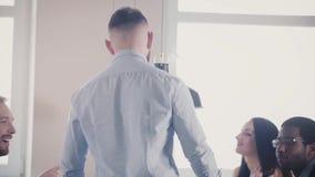 Η κάμερα ακολουθεί το νέο καυκάσιο αρσενικό προϊστάμενο που εμφανίζεται να μιλήσει στους ευτυχείς multiethnic συναδέλφους από τον απόθεμα βίντεο