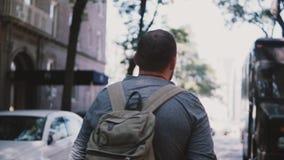 Η κάμερα ακολουθεί το νέο χαλαρωμένο άνδρα ανεξάρτητος εργαζόμενος με το σακίδιο πλάτης που περπατά κατά μήκος της σκιερής οδού σ απόθεμα βίντεο