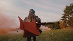 Η κάμερα ακολουθεί το τρέξιμο μικρών κοριτσιών στο πειραματικό κοστούμι αεροπλάνων διασκέδασης με τον καπνό κόκκινου χρώματος στο απόθεμα βίντεο