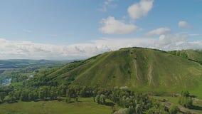 Η κάμερα αυξάνεται βαθμιαία από το έδαφος υψηλότερο και υψηλότερο παρουσιάζοντας όμορφο πράσινο βουνό