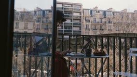 Η κάμερα γλιστρά τη σωστή γυναίκα δημοσιογράφων αποκάλυψης όμορφη χρησιμοποιώντας το lap-top στο ειδυλλιακό μπαλκόνι διαμερισμάτω φιλμ μικρού μήκους