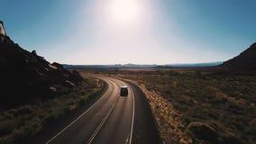 Η κάμερα κηφήνων ακολουθεί το minivan αυτοκίνητο γυρίζοντας αριστερά στο δρόμο εθνικών οδών ερήμων μεταξύ των συναρπαστικών ανοιχ απόθεμα βίντεο