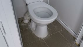 Η κάμερα κινείται ομαλά από από κατω έως επάνω μέσα στον άσπρο δημόσιο θαλαμίσκο τουαλετών φιλμ μικρού μήκους