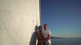 Η κάμερα κινείται προς το νέο αγαπώντας ζεύγος αγκαλιάζει sailboat απόθεμα βίντεο