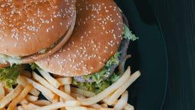 Η κάμερα μεγεθύνει ν στα μεγάλα burgers που βρίσκονται στο πιάτο απόθεμα βίντεο