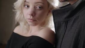 Η κάμερα παρουσιάζει αργά ξανθή μπλε eyed κλίση κοριτσιών στο νέο μαλλιαρό άτομο στο σακάκι απόθεμα βίντεο