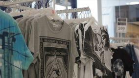 Η κάμερα παρουσιάζει αρσενικές μπλούζες με τις μοντέρνες τυπωμένες ύλες στο κατάστημα απόθεμα βίντεο