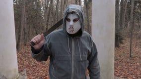 Η κάμερα πλησιάζει το άτομο στη τρομακτική μάσκα και το μεγάλο μαχαίρι αποκριών απόθεμα βίντεο