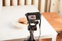 Η κάμερα σε ένα τρίποδο παίρνει cheeseburger στον πίνακα Στοκ Φωτογραφίες