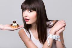 Η κάνοντας δίαιτα γυναίκα που αποκτήθηκε επίασε προσπαθώντας να φάει το κέικ Στοκ Εικόνες