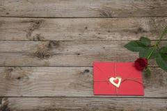 Η κάρτα βαλεντίνων και κόκκινος αυξήθηκε στο αγροτικό ξύλινο υπόβαθρο στοκ φωτογραφίες