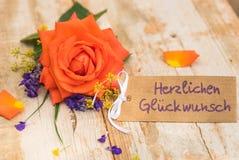 Η κάρτα με το γερμανικό κείμενο, Herzlichen Glueckwunsch, συγχαρητήρια μέσων και πορτοκαλί αυξήθηκε λουλούδι στοκ φωτογραφία με δικαίωμα ελεύθερης χρήσης